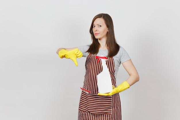 Jonge verdrietig overstuur moe huisvrouw in gele handschoenen gestreepte schort schoonmaak rag squeegee in zak geïsoleerd op een witte achtergrond. vrouw toont duim naar beneden houdt spuitfles met schonere vloeistof. ruimte kopiëren.
