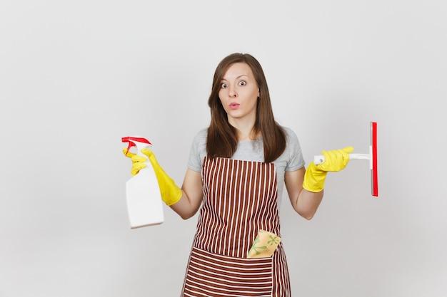 Jonge verdrietig overstuur verbijsterde huisvrouw in gele handschoenen gestreepte schort schoonmaak rag squeegee in zak geïsoleerd op een witte achtergrond. vrouw spreidde handen, houd spuitfles vast met schonere vloeistof. ruimte kopiëren.