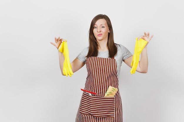 Jonge, verdrietige, overstuur, vermoeide, geschokte huisvrouw in gestreepte schort met poetslap in zak geïsoleerd