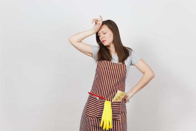 Jonge, verdrietige, vermoeide, huilende huisvrouw in gestreepte schort met poetsdoek, wisser, gele handschoenen geïsoleerd