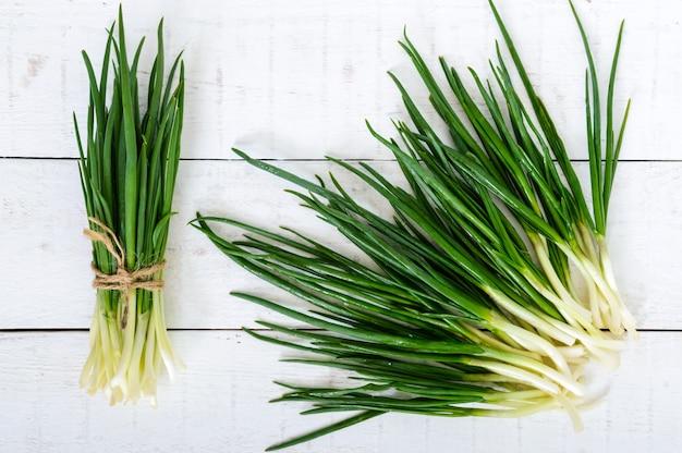 Jonge veren (bladeren) van een groene ui op een witte houten tafel, verzameld in een bundel en verspreid. bovenaanzicht. de eerste lente wordt groen. ingrediënt voor salades.