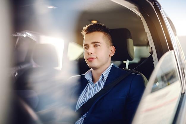 Jonge verfijnde blanke man gekleed smart casual rijdende auto en kijken naar snelweg.