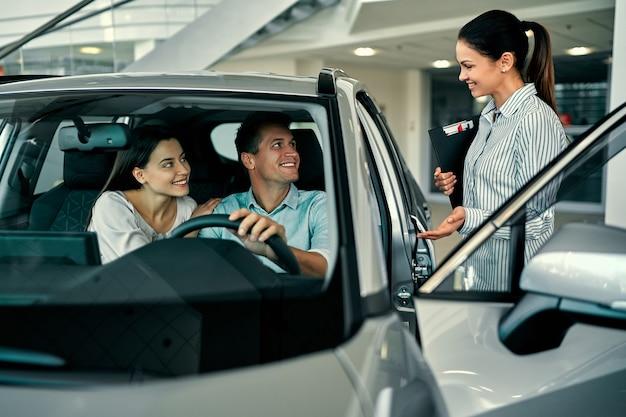 Jonge verkoopster toont een verliefd stel een auto bij een autodealer. een auto kopen of huren.