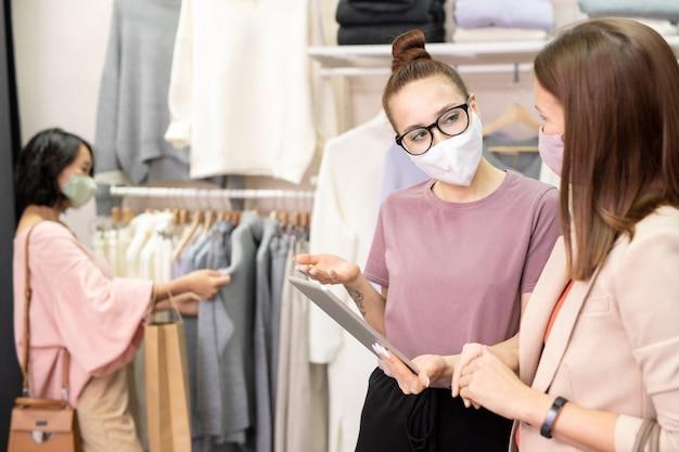 Jonge verkoopsters met maskers die digitale tablet in team gebruiken en nieuwe kledingsets in de winkel bespreken