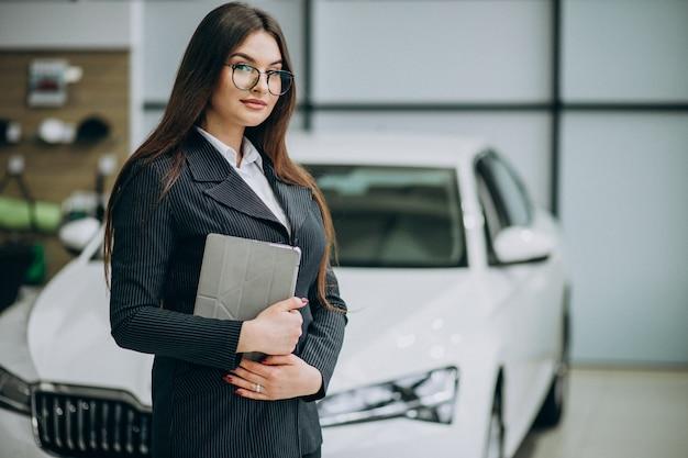 Jonge verkoopvrouw bij carshowroom die zich door de auto bevindt