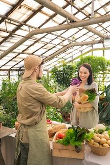 Jonge verkoper van biologisch voedsel die kool in een papieren zak van de klant verpakt terwijl hij verse boerderijproducten verkoopt