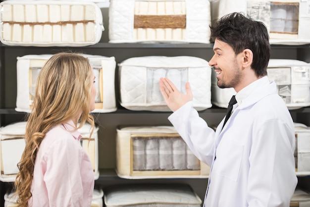 Jonge verkoper vertelt de klant over hoogwaardige matrassen.