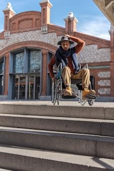 Jonge verlamde latino man in een rolstoel op straat met een gefrustreerde en verontwaardigde hoed voor een trap waar hij niet naar beneden kan