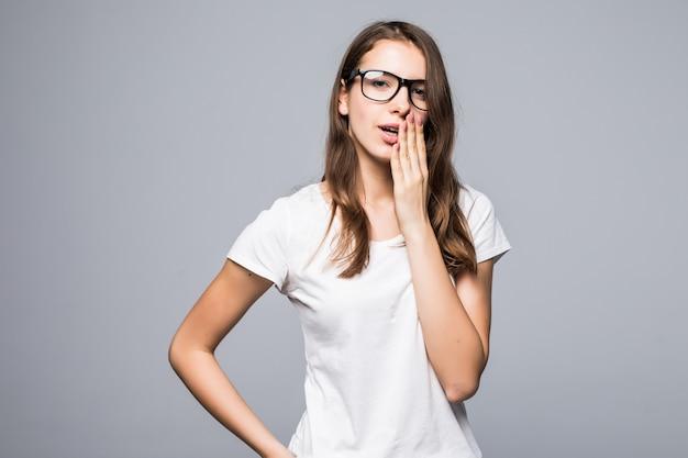 Jonge verlegen mooie dame in glazen in wit t-shirt en spijkerbroek verblijf voor witte studio achtergrond