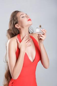 Jonge verleidelijke vrouw in rode jurk die parfum op haar nek toepast. plezier in de geur