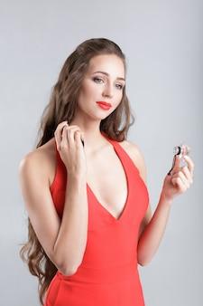Jonge verleidelijke vrouw in rode jurk die parfum op haar nek toepast
