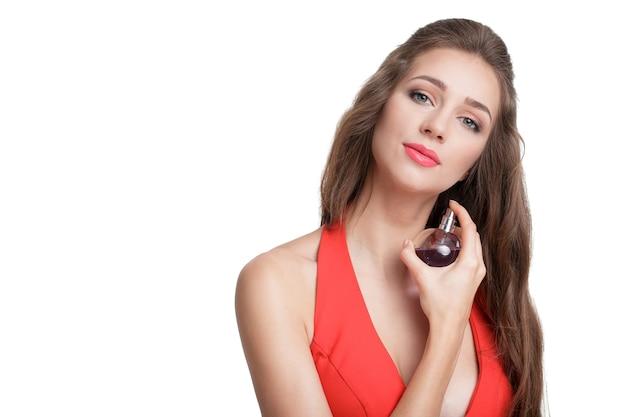 Jonge verleidelijke vrouw in rode jurk die parfum op haar pols toepast