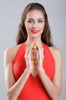 Jonge verleidelijke vrouw in rode jurk met fles parfum
