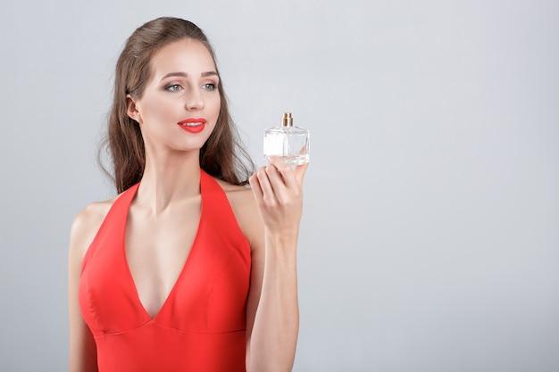 Jonge verleidelijke vrouw in rode jurk met parfum. meisje kijkt naar fles parfum