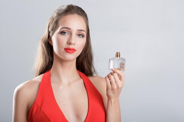 Jonge verleidelijke vrouw in rode jurk met parfum