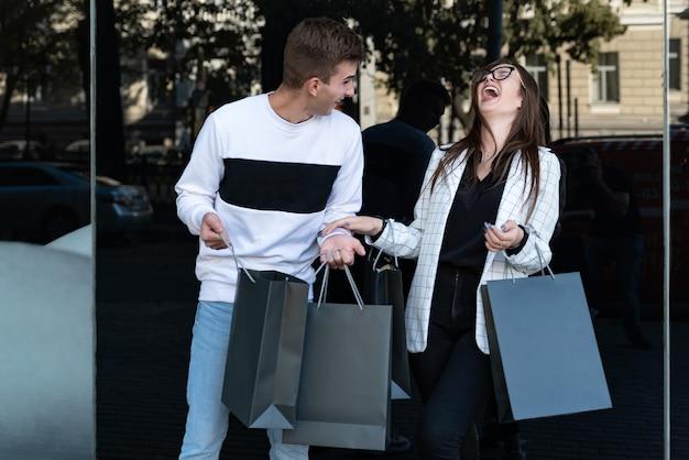 Jonge verliefde paar boodschappentassen dragen en lachen. bespotten. zwarte vrijdag. boodschappen doen. consumentisme.