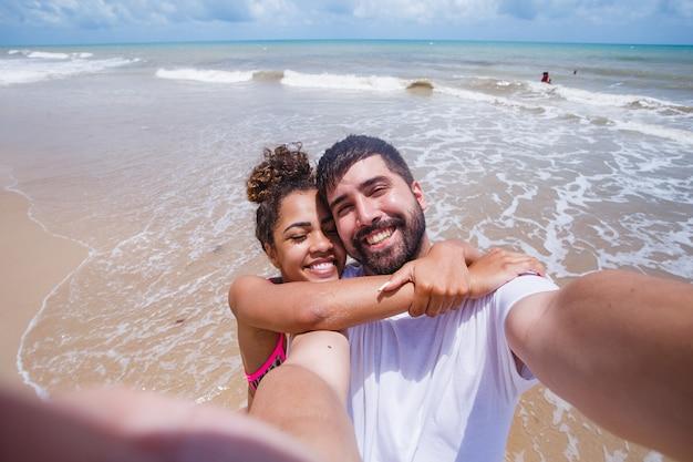 Jonge verliefde paar houden elkaar op het strand selfie te maken.
