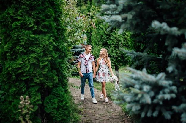 Jonge verliefde paar in het park op een zonnige herfst- of zomerdag. elkaar opzoeken.