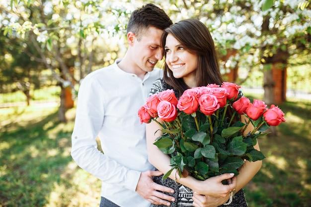 Jonge verliefde paar in liefde, vrouw met bloemen, gelukkig en geniet van de prachtige natuur