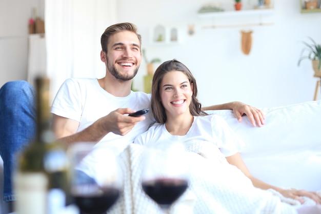 Jonge verliefde paar op de bank thuis tv kijken en lachen, een glas rode wijn drinken