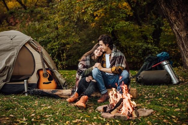 Jonge verliefde paar toeristen ontspannen bij het vuur in de natuur