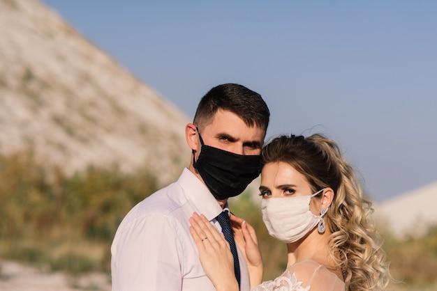 Jonge verliefde paar wandelen in medische maskers in het park tijdens quarantaine op hun trouwdag.