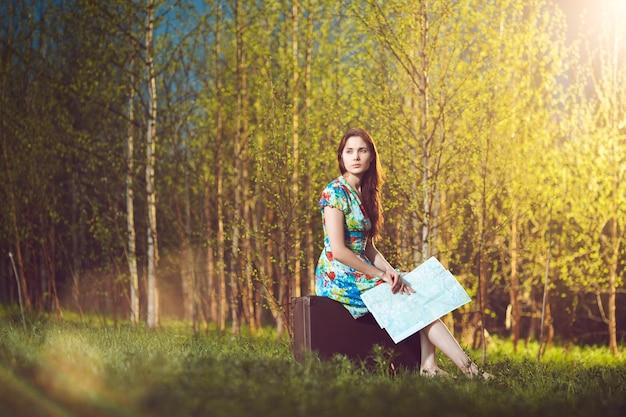 Jonge verloren vrouw met een kaart zittend op een koffer in het bos