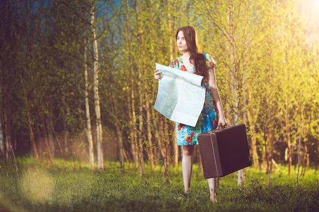 Jonge verloren vrouw met een koffer en een kaart in het bos