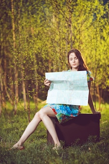Jonge verloren vrouw zittend op een koffer en het lezen van een kaart in het bos