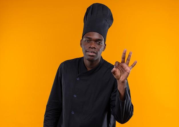 Jonge vermoeide afro-amerikaanse kok in chef-kok uniforme gebaren ok handteken geïsoleerd op een oranje achtergrond met kopie ruimte