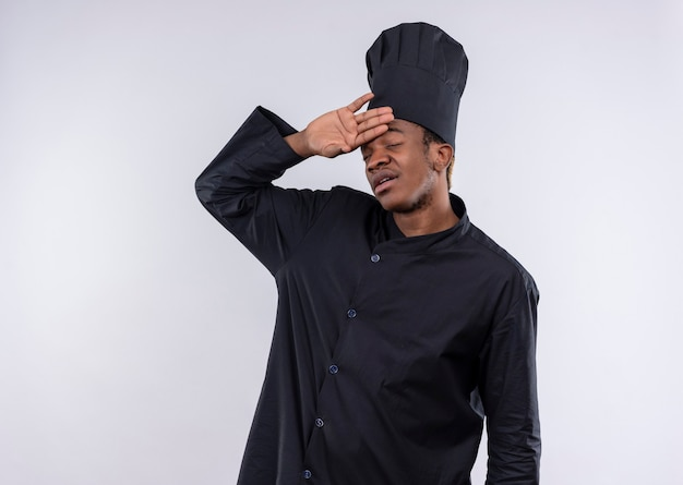 Jonge vermoeide afro-amerikaanse kok in uniform chef houdt hoofd met hand geïsoleerd op een witte muur