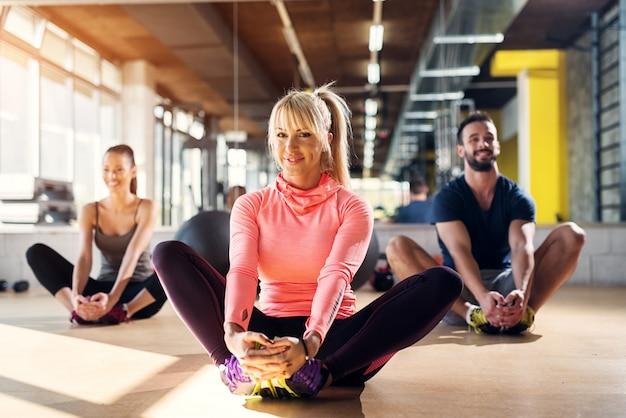 Jonge vermoeide atleten in een gymnastiek die hun spieren na pilatesklasse uitrekken.