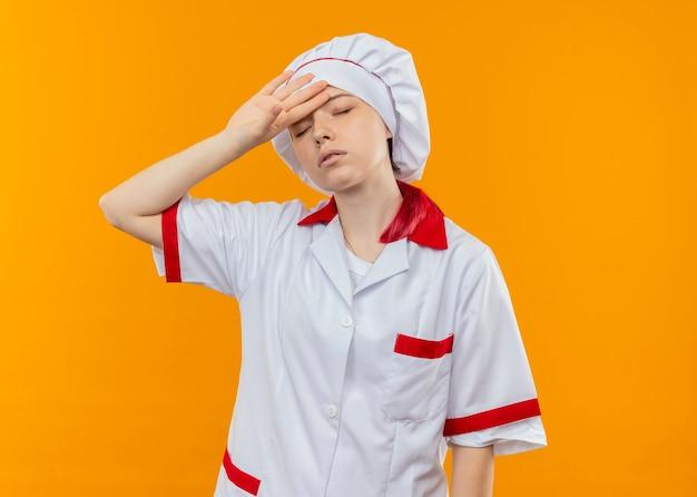 Jonge vermoeide blonde vrouwelijke chef-kok in eenvormige chef-kok houdt hoofd met gesloten ogen geïsoleerd op oranje muur