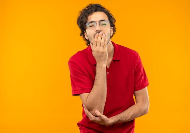 Jonge vermoeide man in rood shirt met optische bril legt hand op mond met gesloten ogen geïsoleerd op oranje muur