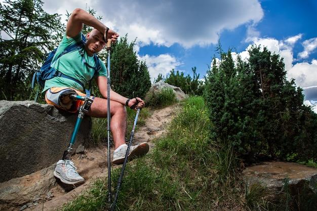 Jonge vermoeide man met prothese die rust na nordic walking terwijl hij actieve sport probeert
