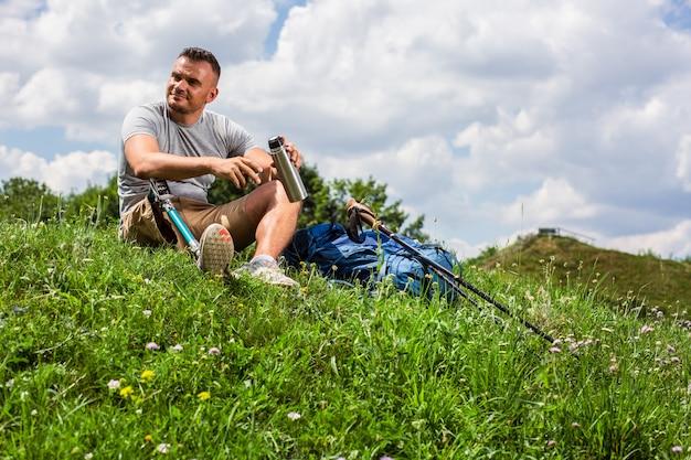 Jonge vermoeide man met prothese die thee drinkt op het gras terwijl hij buiten rust