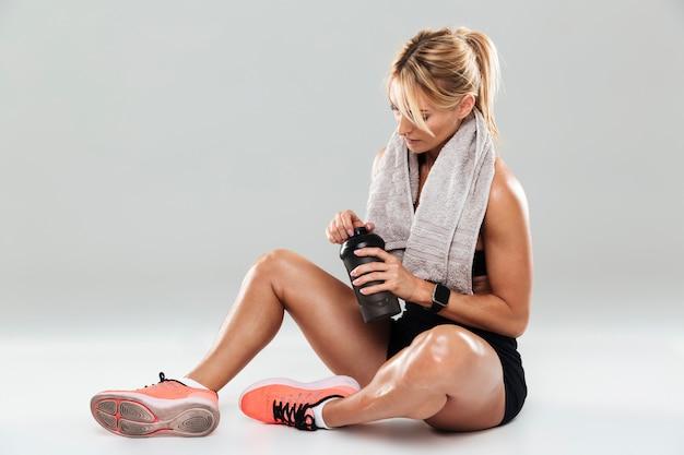 Jonge vermoeide sportvrouw met handdoek op haar schouders