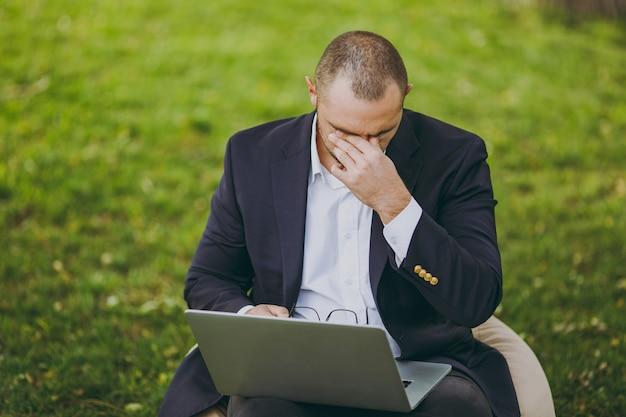 Jonge vermoeide trieste zakenman in wit overhemd, klassiek pak, bril. man zit op zachte poef, maakt zich zorgen over problemen, werkt op laptop pc-computer in stadspark op groen gazon buitenshuis. mobiel kantoorconcept.