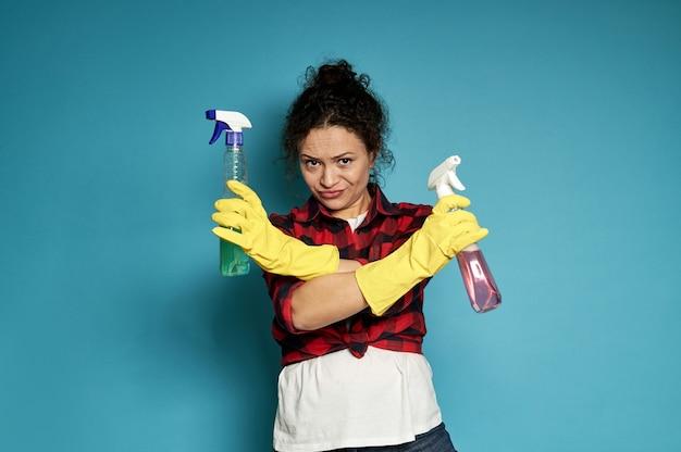 Jonge, vermoeide, uitgeputte, ontevreden huisvrouw sloeg ontkennend haar armen over elkaar, met schoonmaaksprays in de handen