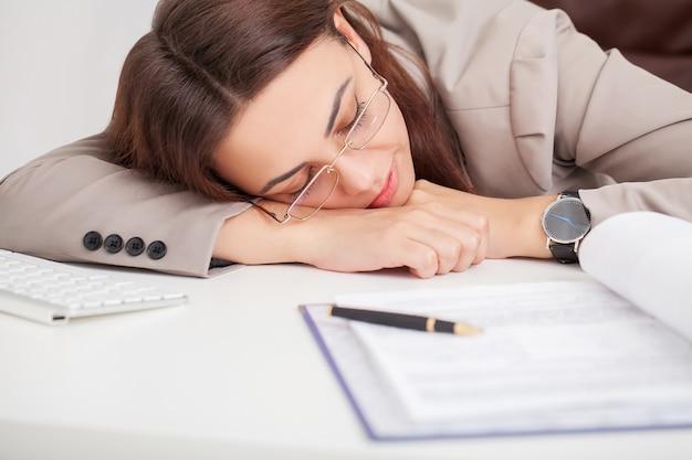 Jonge vermoeide vrouw bij bureauslaap met gesloten ogen, slaapgebrek en zwaar het levensconcept