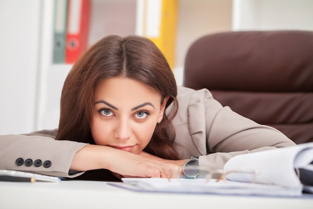 Jonge vermoeide vrouw bij bureauslaap met gesloten ogen