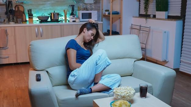 Jonge vermoeide vrouw na het werk die 's avonds voor tv in slaap kijkt. uitgeputte eenzame slaperige dame in pyjama die op de bank slaapt terwijl ze een verveelde film kijkt in de woonkamer en 's nachts de ogen sluit