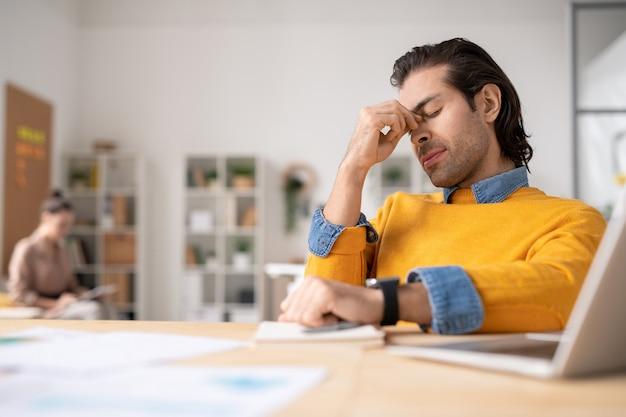 Jonge vermoeide zakenman die zich tijdens het zitten door bureau probeert te concentreren en ideeën voor rapport voor laptop denkt
