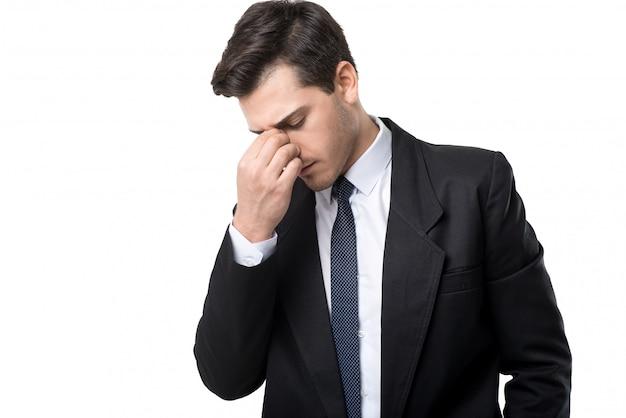 Jonge vermoeide zakenman in gelijkspel en zwart kostuum, dat op witte ruimte wordt geïsoleerd
