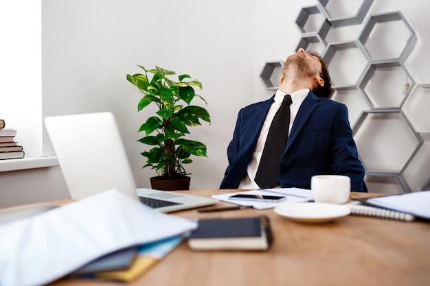 Jonge vermoeide zakenmanzitting op werkplaats, bureauachtergrond.