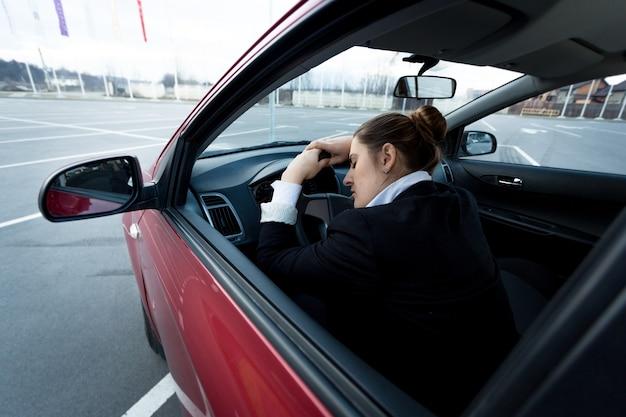 Jonge vermoeide zakenvrouw die in de auto slaapt