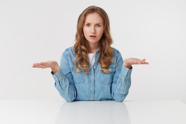 Jonge verontwaardigde blonde dame in spijkeroverhemden, zittend aan de witte tafel en spreidt zijn armen opzij, fronsend en ontevreden kijkt, geïsoleerd over een witte muur.