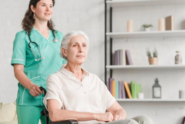 Jonge verpleegster bijwonende gehandicapte senior vrouw zittend op rolstoel
