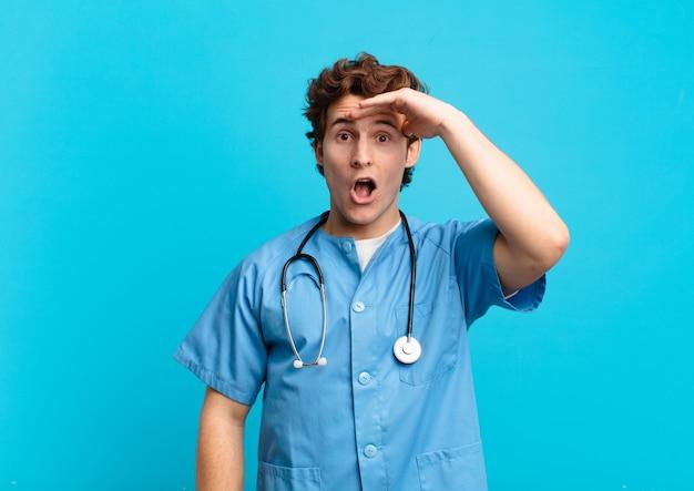 Jonge verpleegster die blij, verbaasd en verrast kijkt, glimlacht en verbazingwekkend en ongelooflijk goed nieuws realiseert