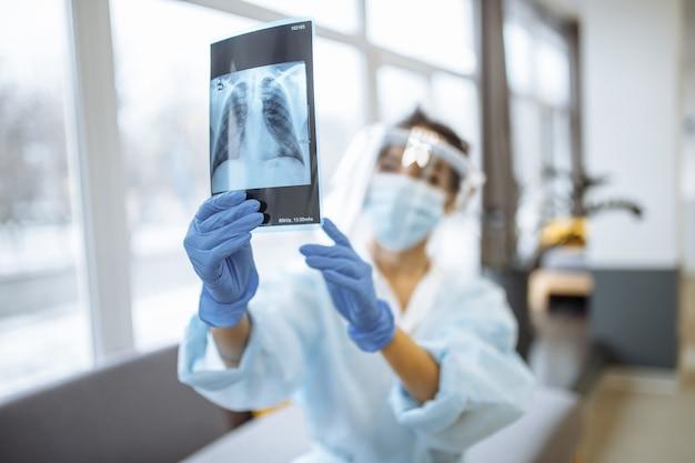 Jonge verpleegster die de röntgenfoto controleert die in de ziekenhuisgang zit. vrouwelijke arts die beschermend gelaatsscherm en medisch masker draagt. coronaviruspreventie en gezondheidszorgconcept.